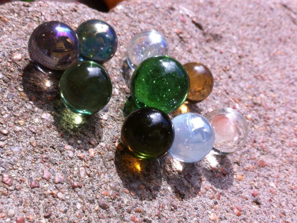 gelbe, grüne, braune weißmilchige Kugeln rollen auf Granit, die Sonne scheint durchsie hindurch und wirft gleißende Schattenlichter unter sie.