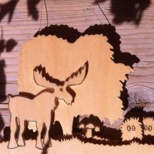 Holzarbeit: Laubbaum mit großem Elch links davor unter dem Baum rechts Pilze und Gras und außen zwei haarige süße Trollkerlchen.. unlasiertes Holz.