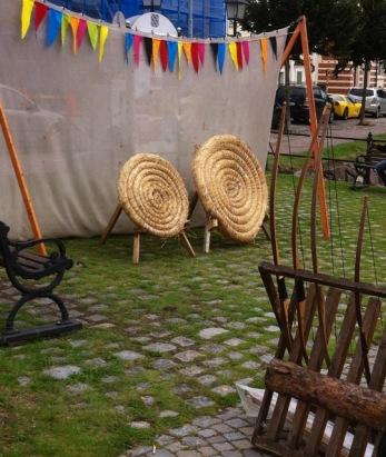 Aus Getreide gebundene Zielscheiben, darüber eine bunte Wimpelkette und diverse alte Holzbögen .. Bogenschießen für die Kleinsten
