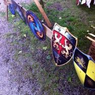 In bunten Farben hängen vier Ritterschilde aus ..schwarz gelb .. rot schwarz und mit Löwenwappen