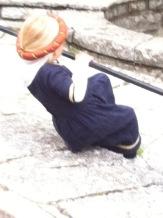 Rückenansicht einer kleinen Maid im blauen Gewand mit rotem Ring und Schleier im Haar.