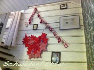 .. hier gehts nach oben, Gemalde von Trollen Stockholm und einer Möwe zieren die Wand, mit einer Birkersohn WeihnachtsKalenderKette und einem Kalender mit Sprüchen für den Papa beides knallweihnachtsrot an weißer Holzwand.