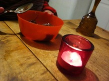 Rosane Kerze auf Holztisch vor Müslischale