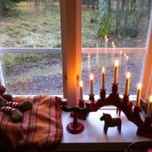 roter Schwippbogen im Schweden Fenster, Elch daneben auf einem Kissen, Holkerzenständer schwedisch bemalt und Dalahästlein